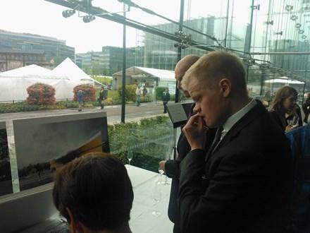 """ALA-arkkitehtitoimiston osakas, arkkitehti Juho Grönholm tarkastelee mietteliäänä voittanutta ehdotusta, joka on nimeltään """"Käännös"""". Taustalla Musiikkitalon ikkunoiden takana näkyy rakennuksen tuleva paikka. Kuva © Matti Niiranen"""